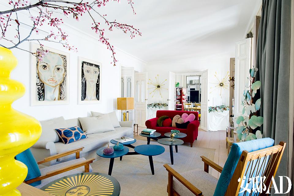 白色基调的客厅里,跳入几点缤纷的色彩,再加上俏皮的人像画作,整个家的感觉年轻而充满艺术活力。客厅里,图片最近处是在L.A.Studio购买的意大利扶手椅;Fornasetti的组合小桌;在Bidart购买的Betiko的茶几;在Anmoder购买的Axel沙发;还有女主人的红色天鹅绒沙发;在Jon Urgoiti购买的意大利网格落地灯;墙上是在Javier López画廊购买的Francesco Clemente的人像画作品。