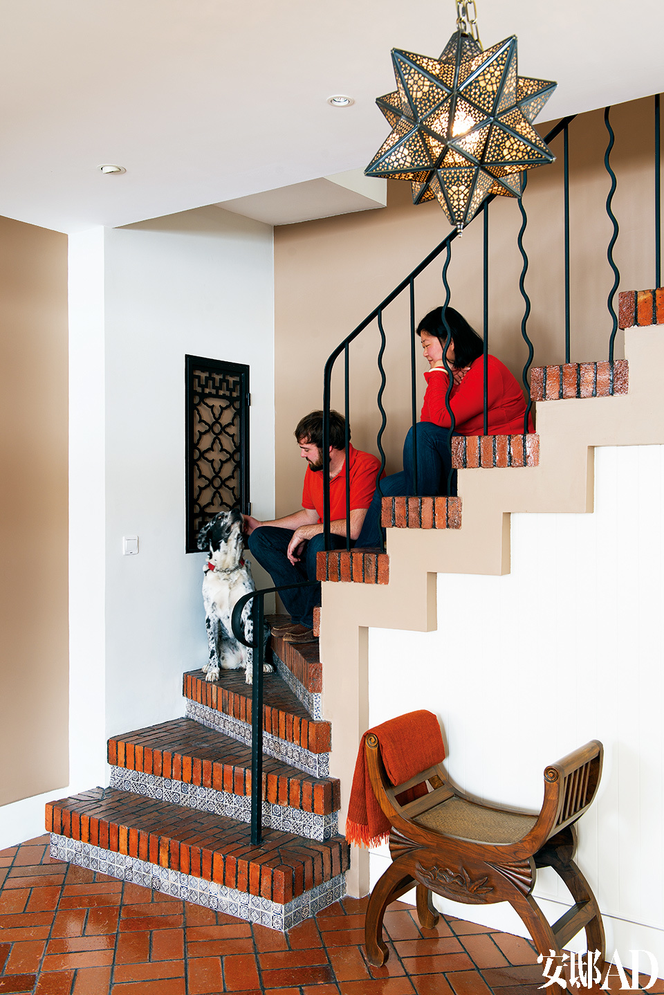 """通往二层的楼梯采用了当地常用的红釉砖,它下面则铺着传统的青花瓷砖,经过切割重新组合,带来新的视觉效果。大狗Danny就是Blake和Lili在北京收养的那只流浪狗,这次坐飞机来新疆""""度假""""了。"""