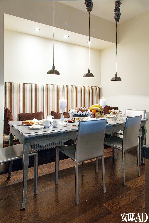 厨房的灰色木桌和金属皮革座椅相得益彰。手工小金属吊灯来自La Maison Retrouvé。条纹天鹅绒靠椅来自Designer Guild,为早餐区增添了温暖舒适的感觉。