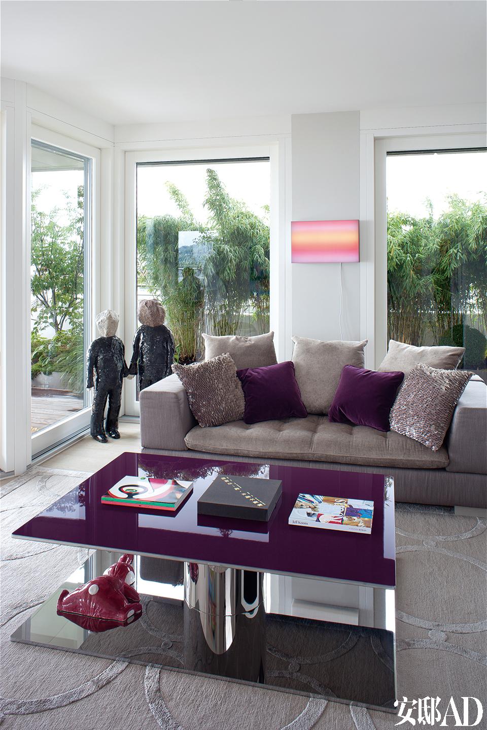 主人对紫色情有独钟,这一色系的所有颜色都频繁地出现在这个家里。客厅里有Martin Székély的淡紫色矮桌,Charlie Point的长沙发,左边玻璃窗前是KlaraKristalova的陶瓷作品《男孩们》(The Boys)。两扇窗之间是LeoVillareal的Light Box。地面上,铺着Rug Company的地毯。