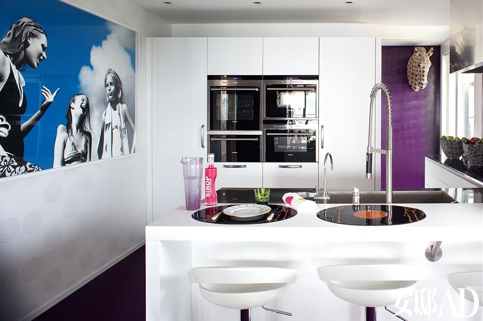 厨房里,左边墙面上是Heidi McFall的作品,搁脚凳是Fly的,水槽水龙头出自KWC,壁橱右上方挂着Joana Vasconcelos的陶瓷驴头。推开餐桌旁的一道紫色推 拉门,明亮的厨房空间便豁然在现在眼前。