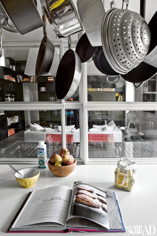 室内厨房与客厅相连,金属框架玻璃 隔断同样带着工业感,又不乏米兰典型的简约精致风格。可以悬挂物品的灯上挂着平底锅,Jacopo的设计,Guido Raffaello制作。