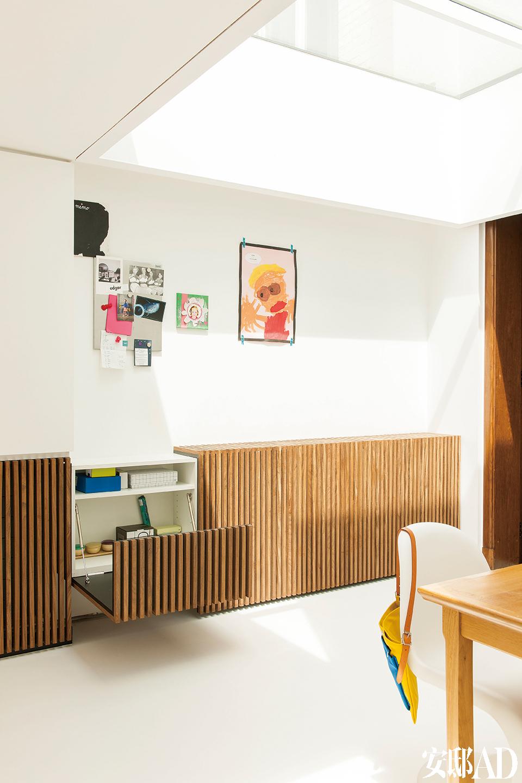 厨房里,白色树脂地板和墙壁营造出一种放松的氛围。橱柜提供了宽敞的储物空间,颜色与起居室原有的玻璃门相呼应。餐桌旁的白色Panton椅令餐厅的整体 感觉柔和了许多。