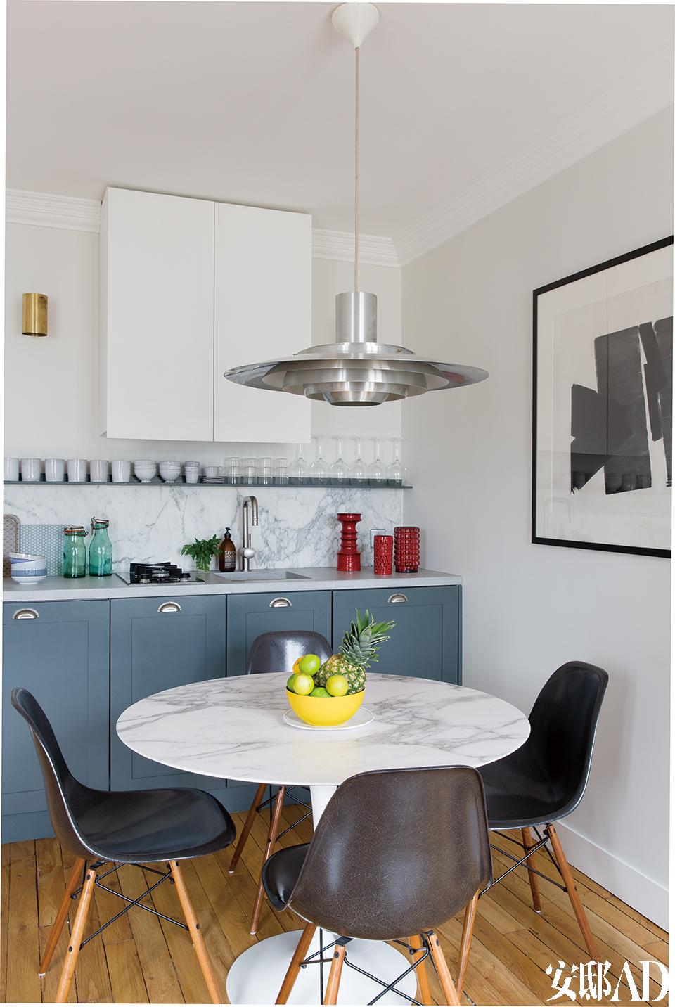 """吊柜被喷涂成了与墙体相同的白色。""""让越多的东西'消失'在房间里,你就会获得越大的空间感。""""餐厅和厨房区,Tulip餐桌由Eero Saarinen设计,原版的Eames DSW餐椅来自马赛的Atelier 159,磨砂铝制吊灯由Preben Fabricius 和Jorgen Kastholm设计于1965年,购自巴黎的Galerie Espaces 54。定制厨房是Christophe自己设计的,橱柜门由MDF制作,喷涂了Farrow & Ball漆。水泥操作台面上有3只20世纪60年代的红色意大利和德国花瓶,防溅板选用了大理石材质。"""
