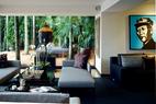 郁郁葱葱的棕榈树和低矮灌木不仅衬托着室内的深沉色调,还构成了整个家的天然屏障,保护着主人畅享安宁。主客厅中,落地玻璃窗营造出身处雨林中的静谧感觉。沙发均为定制品,使用了纽约和伦敦设计师创作的面料。巨大的佛首像来自普吉岛,非常沉重,Marie记得当时搬卸时用了10名工人。右侧墙上的毛泽东头像画作是李山创作的油画作品《胭脂01号》。
