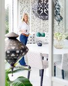 Helen Lindman站在雕花玲珑的露台上,白色系的坐卧沙发和屏风仿佛将人带到了地中海。