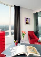 女主人的书房占据了公寓楼的一角,弧形大窗带来完美视野。墙上的一幅木刻综合材料小画的作者是郑维,红色抽屉柜来自Magis品牌,带脚踏的红色真皮扶手椅由Molteni&C出品。