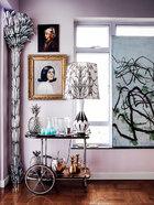 家中的艺术品和装饰都是女主人多年旧藏,它们共同营造出一种梦幻氛围,将人带入不同于现实的另一时空。在墙角处竖立的大型银叶棕榈树落地灯是上世纪50年代的法国设计,古董银菠萝冰桶和烛台均来自JL Collection。银质覆山羊皮滑轮小车是Aldo Tura的设计,来自上世纪50年代。玫瑰木加陶瓷质地台灯是上世纪50年代的德国设计,同样来自JL Collection。