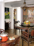 """玄关边上的用餐空间,其吊灯为父亲从洛杉矶一路""""抱""""回来的。柚木圆形餐桌为叶裕清在缅甸买的。餐椅为中国清末的云石太师椅(清末),墙上挂着老西藏唐卡。"""