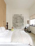 主卧室中,墙上的艺术品由Christopher Wool创作,木刻人像、牛角椅是非洲部落艺术品,落地灯由Christian Liaigre设计。