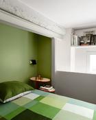 """悬空的卧室里,只有一张床、一个由Lonna Vautrin设计的""""Baobab""""床头柜(来自Moustache)和一个由Charlotte Perriand设计的旋转百叶壁灯(来自Nemo Cassina)。铜制茶具来自CFOC,床单来自Hay chez Sentou。"""