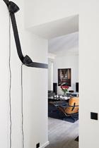 从餐厅门口看向客厅,浅色的墙面和地板上,家具和艺术品都选择了深色,对比非常鲜明。近处是一只古董的Eames躺椅Charles,前景白色墙壁上的黑色线条和灯头是餐厅中Diamond Boxes壁灯的一部分,由 Normal Studio出品。