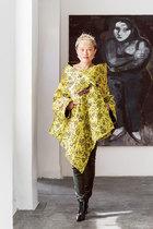 """主人: 韩枫,作为1985年就移居纽约的""""老土中国人"""",从当年勇敢宣称自己""""要做时装设计师""""起,就注定会拥有不平凡的人生轨迹。她以用面料商店的废布头儿做 成的围巾起步,在1994年推出了首个成衣系列,从此每年在纽约举办两季的时装秀,成为最早成功征战纽约秀场的中国时装设计师,拥有不少明星客户。除了时 装,她还涉猎陶艺、玻璃制品甚至博物馆室内装饰等等跨界设计。2004年,韩枫回上海开设了自己的品牌店铺,后来索性将工作室直接搬回上海。2005年她 参与了英国大导演Anthony Minghella指导的新版歌剧《蝴蝶夫人》,为其设计舞台服装,此后又完成了多部戏剧的服装设计。如今她在中美之间穿行,像一座桥梁般为好设计的共享 尽自己的一份力量。韩枫穿着自己设计的服饰站在卧室中,背景墙上挂着画家张恩利以自己的太太为模特而创作的肖像画。和暖的冬日阳光通过家中的大窗洒向她的 金色披肩式华服,令韩枫整个人都光彩熠熠 。"""