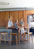 巨大的岛台给开放的生活区带来了活泼的个性,这里也是女主人和4个孩子最喜欢围坐讲笑话的地方。餐厨空间充满几何感,宽敞的操作台成了生活区的一个亮点,橡木吧台凳是复刻版的上世纪50年代设计,来自EEMeyer。