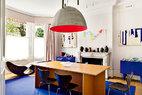 """无处不在的艺术品与经典设计为每日生活带来无穷乐趣与创意激情,它们如同日晷般刻量着时间对这个艺术之家的浸淫。餐厅里Donald Judd设计的用胶合板制作的桌子上是Ingo Maurer设计的直径1米的巨型铝制吊灯""""Pierre Ou Paul""""。独特的维多利亚风格壁炉两侧有两个一样的电光蓝色斗柜,它们是西班牙设计师Jaime Hayón为BD Barcelona设计的作品。每个斗柜上都摆放着美国艺术家Caio Fonseca的作品。壁炉的台架上摆放着墨西哥艺术家Pedro Ramos Morales设计的瓷罐,上方的霓虹灯""""Fucking Beautiful""""是英国艺术家Tim Noble和Sue Webster在2008年创作的作品。窗户前面摆着的是不锈钢制成的躺椅Loop Loom,它是1992年Ron Arad挑战万有引力定律而创作的。"""