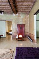 """""""我喜欢中国的文化和艺术,甚至中国的家具。它们看起来如此熟悉,却又充满异国风情。""""起居室的左边可通往卧室,右边则是厨房。Meritalia绒面沙发,Calder地毯,最新的Mollino座椅,中式朱红大柜和圆形矮桌均购于罗马。"""