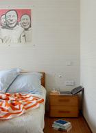 主卧室中,墙上的画作是艺术家韩湘宁的纸上作品,床头柜由日本设计师创作,床上的橘红色几何盖毯来自Lane Crawford连卡佛。
