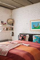 """白砖墙、暖气片和水泥天花板保留着 硬朗的工业感,彩色床品和画作则调和出暖暖的居家温情。主卧室中,床上的床单来自印度孟买,两只抱枕是Alex用来自英国集市的布料制作而成的。墙上的画作是Patrick Hughes在1981年的作品《The Rest of the Rainbow》,它是Alex的最爱。床头的""""蝴蝶效应""""台灯由Ben的学生Pu Tai为Peachy品牌设计,开灯时你会产生一种蝴蝶在扇动翅膀的错觉。白色搁架上的红木化妆镜由Robert Heritage设计于1965年,Archie Shine出品,两只白色不规则花瓶来自Spin。"""