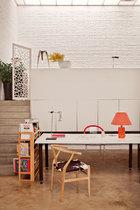 平时的办公桌,摇身一变就是宴客餐桌;沙发区设在台阶上面,也不是传统意义的 客厅。打破常规,唯我所用,这才是为家做主的自信。 Alex的工作室中拥有很多Ben为她量身定制的家具。一面巨大的白色储物柜可以双向开门,另一侧就是上层客厅区的储物柜,柜顶上的一只多面抛光不锈钢小 凳是年轻设计师张周捷的作品,他曾经是Ben在圣马丁艺术学院的学生。办公桌下还隐藏了笔记本的电源走线,桌上左边的台灯是Ben用一只虎头牌手电筒做的 设计,右边的红色台灯则是他的父亲David Hughes先生在1970年代制作的,使用的是苏联时期的伏特加酒瓶。最前面的扶手椅是Hans Wegner设计的Wishbone椅,这种应用小马皮的版本现在已经非常少有。