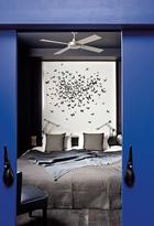 """主卧室与蓝色更衣室相连,床头在法国艺术家Manon Tricoire 的手中,化作了日本煅烧纸蝴蝶的天堂。法国艺术家Manon Tricoire为主卧室设计了诗意的""""蝴蝶墙"""",日本煅烧纸制成。由Richard Sapper设计的Tizio床头灯出品自Artemide,门把手为Chofa品牌。"""