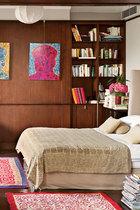 """一家人都乐于在旅行中发现美,带回的物品让美好时光重现,""""这些记忆甚至比物品更重要!""""主人有睡前阅读的习惯,因此干脆请衣柜让出一部分空间放书。墙上的艺术品来自薛松的版画《毛泽东》。从新疆当地人手里买回的地毯,部分盖住了深色的地板,感觉温暖,只是它们在长时间里会散发出羊的""""性感""""味道,却阻挡不了女主人一见到它就想起一家人在旅行中的愉快时光。"""