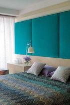 卧室里如海洋般浓艳的蓝色调中,条形波纹的Missoni床品又增添了一份优雅的层次感。主卧中低矮木墙面的上方安装了湖蓝色天鹅绒面料的软包,天花板将顶灯隐藏了起来。Poliform品牌的Arca睡床一侧摆放了一座Tolomeo台灯,床品和旁边的圆形脚凳同样使用了蓝绿色的Missoni床品面料。