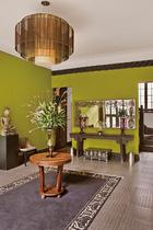 入户的门厅很大,绿色的墙面给老房子一种焕然新生的感觉。墙上的镜面是意大利18世纪的古董,彩色玻璃器皿则来自上海的旧货市场。