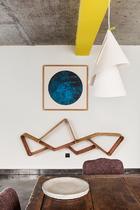 """无论画作还是设计品,彼此找到恰当的呼应,才是真谛!新式的""""齐云""""客房一楼,中式古董桌搭配着翻新的椅子, 墙面上汤国的水墨画和Sandeep Sangaru的竹书架形成了几何 元素的组合,亮黄色的横梁与Ingo Maurer的Willydilly吊灯则带 来轻松、活泼的气氛。"""