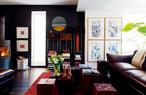 """二楼的客厅中,实木模块组合成的木墩充当了茶几,由Momentum出品。茶几上的一组木质摆设其实是纱线生产和染色时所用的木轴,它们是Arnd 25年前从希腊一个废弃的工厂中""""抢救""""回来的。来自Natuzzi的皮沙发拥有流畅的微曲线和令人舒适的比例,地毯则是Ligne Pure生产的""""梦幻系列(The Dream)""""。靠墙的一段橘色木条显示了希腊传统的接木方法,它和两个中式古董木匣放在一起,定制的不锈钢支架、黑色背景墙和那面圆镜都为这个角落增色不少。"""