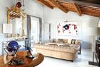 简洁的建筑结构为经典家具提供了最好的背景,意大利家具的精湛品质让整个空间显得高级而不做作。起居室一角。沙发左右的两扇门都通向餐厅。墙上挂着意大利艺术家Paolo Ceribelli创作的画。