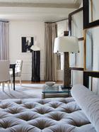 后客厅另一侧的墙面上挂着一幅André Marfaing在1970年的画作,一旁顶着石膏雕塑的桃花心木黑色立柱、近处的桃花心木镶玻璃折叠屏风和长椅都由Thomas工作室出品,茶几上青铜 灯柱的台灯是Hervé Van Der Straeten的作品,羊毛地毯则来自Martin Patrick Evans。客厅分前后两个部分,后客厅原为餐厅,一张大躺椅的加入,使房间的功能不再单一。