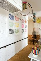 """家中从地面到天花板都选择了浅色背景,五彩斑斓的艺术品在其中欢快地跃动。天花板上网格状作品名为""""Thank YouSilence"""",Ugo Rondinone创作。布满彩色螺丝钉的墙面由Mathieu Mercier创作,墙上的版画来自Allen Ruppersberg,天花板上悬挂的彩色吊饰出自Tobias Rehberger之手。右下角的花瓶名为""""Painting With Giotto"""",作者为Fernando Brizio,""""Carrara""""桌来自Jasper Morrison。"""