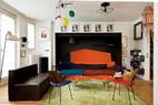 客厅另一侧,Bouroullec兄弟设计的沙发被做成了床的形状,红色漆面、钢材质的茶几是Marc Newson的设计,棕色皮质沙发来自Martin Szekely;蓝色和红色座面椅子的设计师为Robin Day。绿色地毯来自Fabrice Hybert,彩色不规则吊灯仍是Gino Sarfatti的设计。