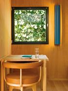 黑框方窗是设计的一大特色,画框般将满目绿意引入室内。桌子旁边是夏洛特设计的LC7摇椅的木质凳脚独家版本。