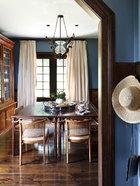 与起居室相连的餐厅,选用了蓝色的墙面和米色的窗帘,搭配深胡桃木色,营造了度假屋沉静、缓慢的氛围。