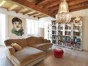 艺术品与镜面书架诉说着主人时尚的家居主张,也将深色木质天花板带来的压抑感一扫而空。客厅中,木质的天花板与地面令人感到一种置身于乡野木屋的错觉。Ginevra沙发、Galahad水晶吊灯、Daydream镜面书架由 Alessandro La Spada和Samuele Mazza设计,全部来自Visionnaire。墙上的画作出自画家Domenico Grenci之手。