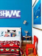 """"""" 我坦白自己对上世纪50年代设计的钟情,但也醉心于意大利风情,我爱美式、赞美法式,也倾倒于巴西式的惬意。""""Montse的儿子Jaime的房间被重新漆成了青瓷蓝色。墙壁上发亮的霓虹字样是Mónica Sánchez Robles的作品。右边墙上是Ricardo Labougle的摄影作品。Matégot设计的金属壁灯是在EL 8购买的,Luis Galliussi设计的床头柜和宜家家居的Mammut椅带来一丝有童趣的设计感。床上用品来自Olatz,靠垫来自Svenskt Tenn,中亚刺绣床罩是Tomás Alía送的礼物。"""
