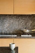 厨房墙壁选择朴实的岩石,其桌上的陶杯,是冯亚敏收藏的韩国艺术家作品。