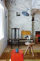 客厅一角,粗粝的墙面、经典的设计与旧迹斑斑的古董家具,共同散发出静寂的时光味道。艳丽的橙色陶质边桌OKO成了客厅中的亮点,老式的土耳其地毯呼应着印尼风格的榆木凳子以及一把19世纪的中式古董椅。LeCorbusier设计的壁灯 Lampede Marseille是Nemo Cassina的产品,墙角的油画都由主人Guillaume Terver自己创作。