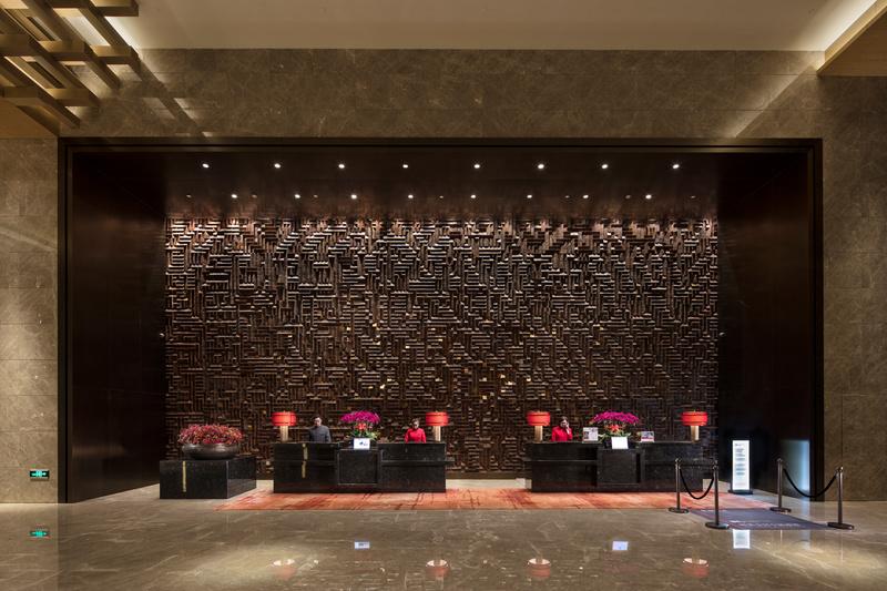 """酒店前台的背景墙更是设计成了""""城关""""样式,实木与琉璃的结合,巧妙地将图片"""